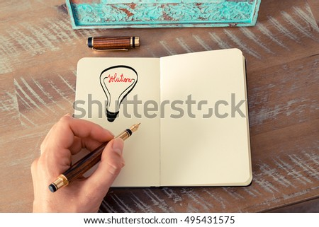Retro effect and toned image of a woman drawing a lighting bulb with fountain pen on a notebook. SOLUTION symbol and concept, copy space available for text