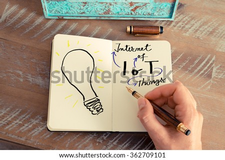 Retro effect and toned image of a woman hand drawing a light bulb next to IOT INTERNET OF THINGS text with a fountain pen on a notebook. Copy space available, ideas creativity conceptual image - stock photo