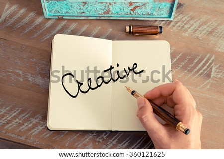 Retro effect and toned image of a woman hand writing a note with a fountain pen on a notebook. Motivational concept with handwritten text CREATIVE