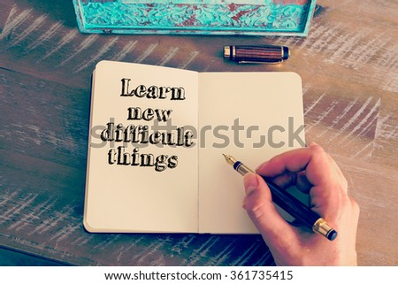 Retro effect and toned image of a woman hand writing a note with a fountain pen on a notebook. Motivational message LEARN NEW DIFFICULT THINGS as concept for self improvement - stock photo