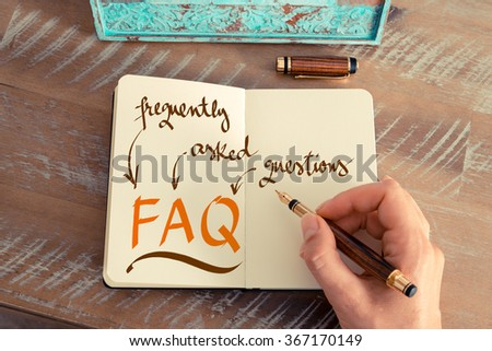 Retro effect and toned image of a woman hand writing a note with a fountain pen on a notebook. Handwritten text FAQ FREQUENTLY ASKED QUESTIONS, business success concept - stock photo