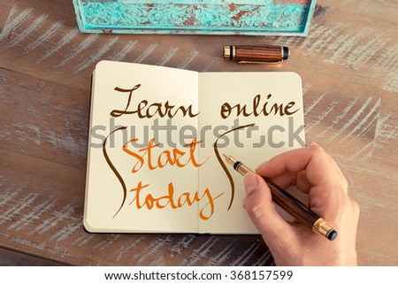 Retro effect and toned image of a woman hand writing a note with a fountain pen on a notebook. Handwritten text LEARN ONLINE START TODAY, motivation concept - stock photo