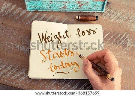 Retro effect and toned image of a woman hand writing a note with a fountain pen on a notebook. Handwritten text WEIGHT LOSS STARTS TODAY, motivation concept - stock photo