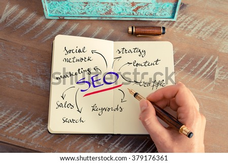 Retro effect and toned image of a woman hand writing a note with a fountain pen on a notebook. Business concept image with handwritten text SEO as SEARCH ENGINE OPTIMIZATION - stock photo