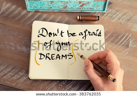 Retro effect and toned image of a woman hand writing a note with a fountain pen on a notebook. Handwritten text DON'T BE AFRAID OF YOUR DREAMS as business concept image - stock photo