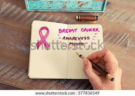 Retro effect and toned image of a woman hand writing a note with a fountain pen on a notebook. Hand drawing of pink ribbon as breast cancer awareness month symbol, empty copy space available