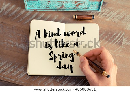 Retro effect and toned image of a woman hand writing on a notebook. Handwritten quote A kind word is like a Spring day as inspirational concept image - stock photo