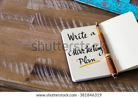 Retro effect and toned image of notebook next to a fountain pen. Business concept image with handwritten text WRITE A MARKETING PLAN , copy space available