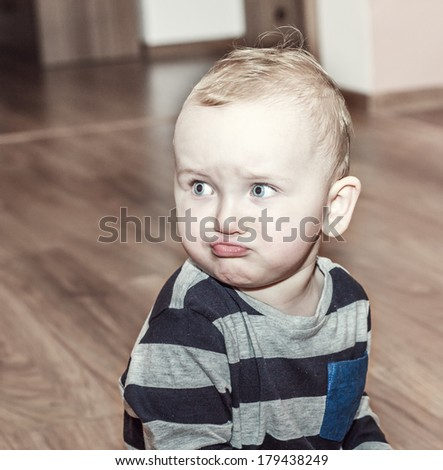 retro effect - angry boy sitting on the wood floor and looking aside - stock photo