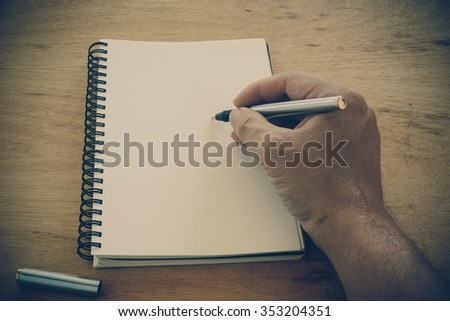 Retro effect faded and toned image of a writing a note with a fountain pen - stock photo