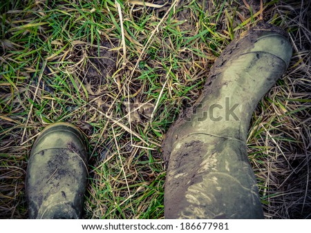 Retro Faded Photo Of Dirty Rubber Boots In The Countryside - stock photo