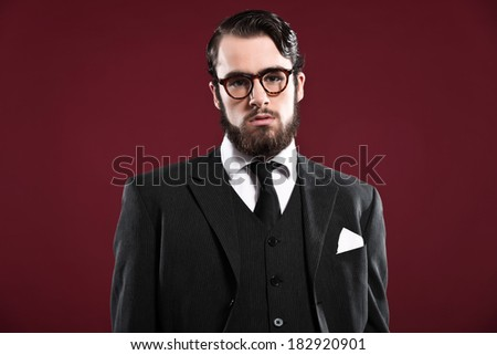 Retro 1900 fashion man with beard wearing grey suit black tie and glasses. Studio shot against red background.