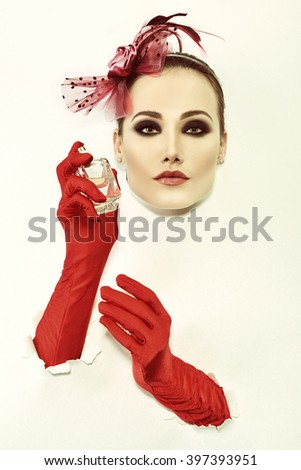 Retro fashion portrait of young woman with red gloves and bottle of perfume, image toned. - stock photo