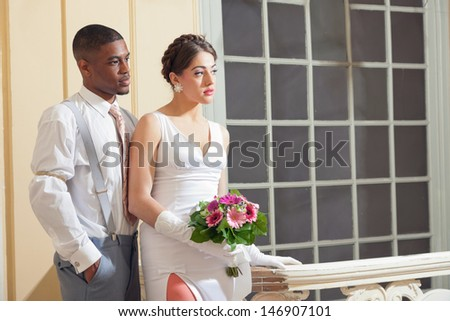 Retro fashion romantic wedding couple in old classic interior. Mixed race.