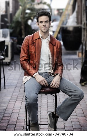 Retro feel portrait of young man outdoors in leather jacket sitting in chair - stock photo