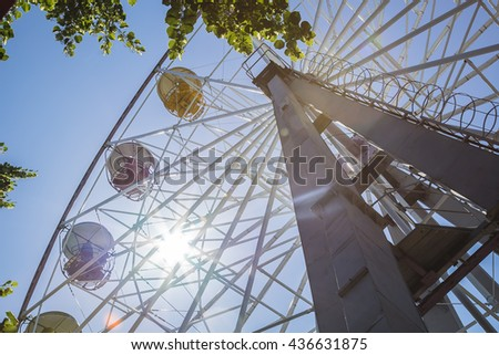 Retro Ferris Wheel on Blue cloudy Sky and solar flare - stock photo