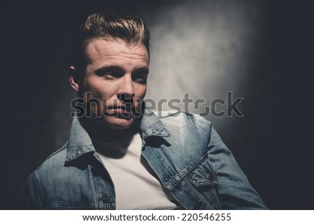 Retro fifties cool fashion man wearing white shirt and jeans jacket. Gray wall.