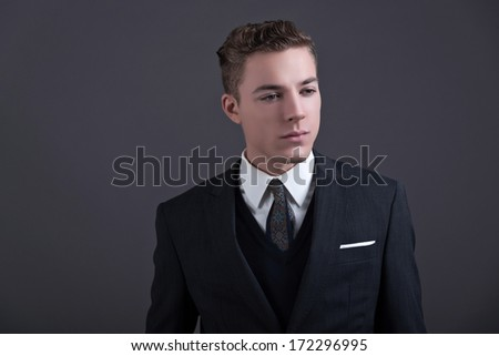 Retro fifties fashion young businessman wearing dark suit and tie. Studio shot against grey.