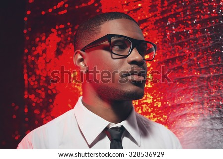 Retro fifties hispanic man with glasses in white shirt and black tie. Against red reflective background. - stock photo