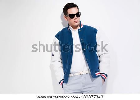 Retro fifties sportive fashion man wearing blue baseball jacket and dark sunglasses. Studio shot against white. - stock photo