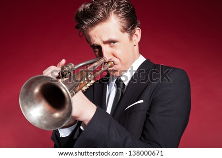 Retro fifties trumpet player wearing black suit. Playing trumpet. Red wall. - stock photo