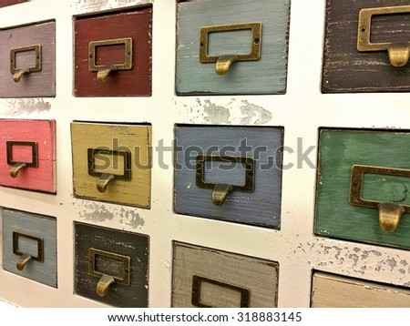 retro filing cabinets with colorful drawers and brass plate handles - stock photo