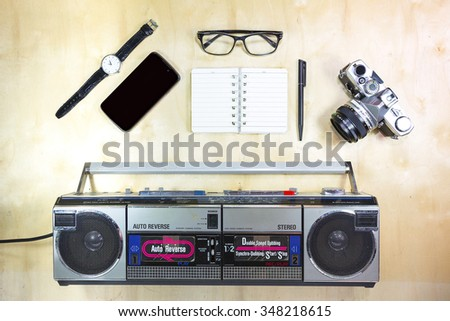 Retro Film Camera, watch, smart phone, glasses, notebook and radio isolated on wood table. - stock photo