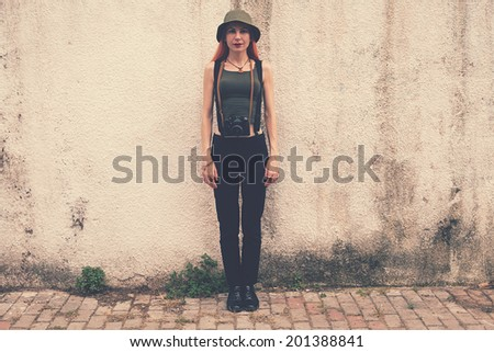 retro filtered photograph of a hipster girl with an analog camera - stock photo