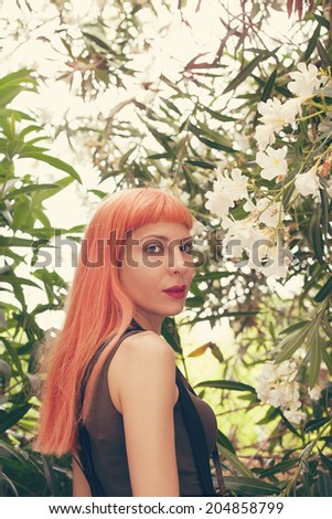 retro filtered photograph of a hipster girl with blonde and pink hair - stock photo