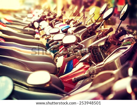 Retro filtered picture of scooter in a row. - stock photo