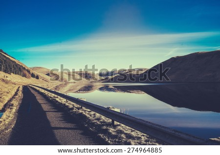 Retro Filtered Scenic Landscape Of An Empty Road By A Lake In Scotland - stock photo