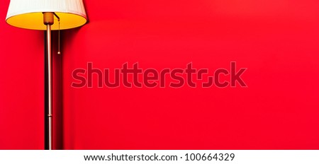 Retro floor lamp near red wall with lots of copyspace. Nobody - stock photo