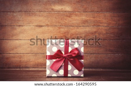 Retro gift on wooden table. Photo in vintage color image style. - stock photo