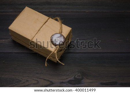 retro giftbox tied with rope and wax seal on black wooden table, photo with copy space