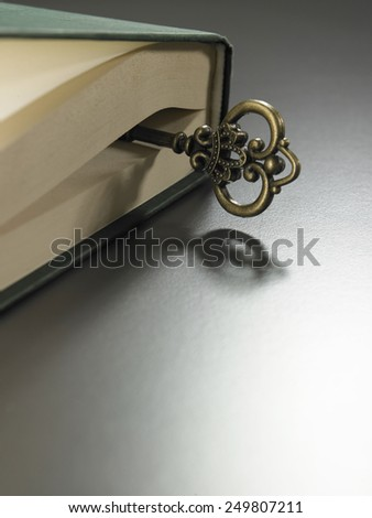 retro golden key on thick hard cover book - stock photo