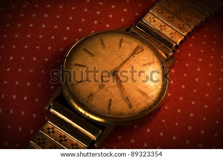 Retro golden wristwatch close up on red vintage cloth background.