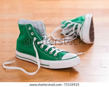 Retro green sneakers left on wooden floor - stock photo