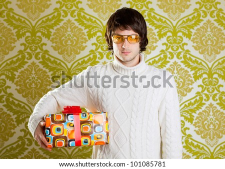 retro hip young man glasses holding  psychedelic gift box on wallpaper - stock photo