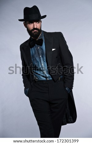 Retro hipster 1900 fashion man in suit with black hair and beard. Wearing blue jeans shirt, hat. Studio shot against grey.