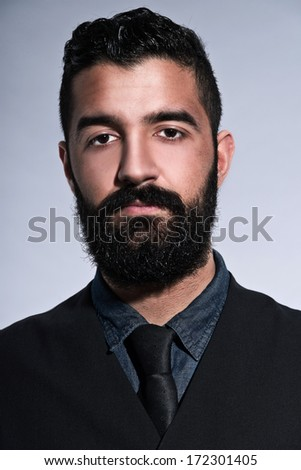 Retro hipster 1900 fashion man in suit with black hair and beard. Wearing gilet plus tie. Studio shot against grey.