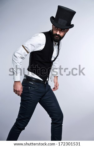 Retro hipster 1900 fashion man with black hair and beard. Wearing black hat. Studio shot against grey.