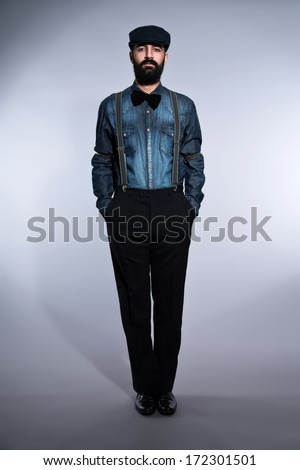 Retro hipster 1900 fashion man with black hair and beard. Wearing blue jeans shirt, cap. Studio shot against grey.