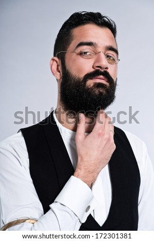 Retro hipster 1900 fashion man with black hair and beard. Wearing vintage glasses. Studio shot against grey.