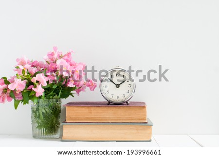 Retro home decor: a stack of books, flowers and a vintage alarm clock on a white wall shelf - stock photo
