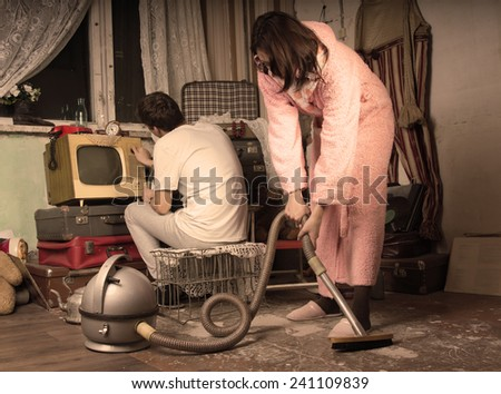 Retro housewife in her dressing gown and slippers cleaning a messy living room with a vintage vacuum cleaner while her husband watches television on an old TV set, aged style toning - stock photo