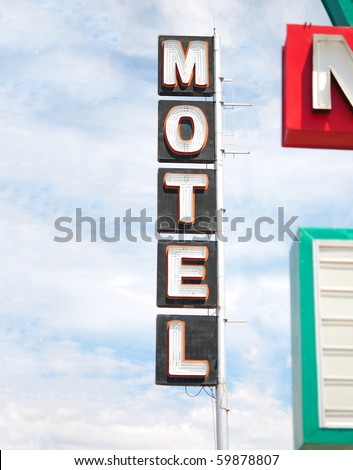 Retro iconic American west motel road sign with blue sky background - stock photo