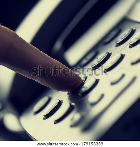 Retro image of a finger pressing a number button on the telephone to make a call. - stock photo