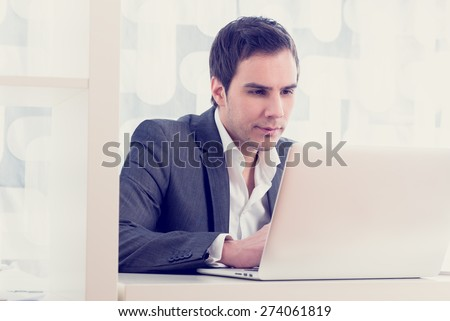 Retro image of a handsome young businessman typing or working on a white laptop computer keyboard, low angle view from the back of the computer. - stock photo