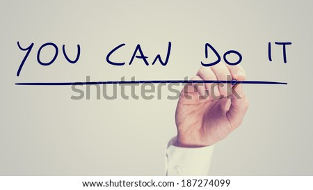 Retro image of a man writing a motivational message - You Can Do It - on a virtual interface or screen with a marker as a sign of encouragement, with copyspace for your text. - stock photo
