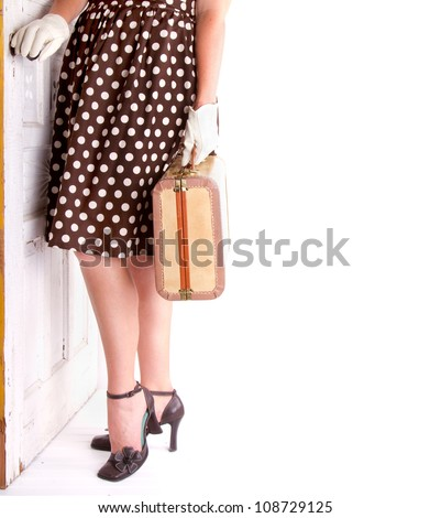 Retro image of a woman holding vintage luggage with a vintage door - stock photo